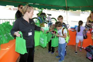 Phyllis Head, community liaison at Tanner Health System's Get Healthy, Live Well, passes out goody bags during an event recognizing Carrollton elementary and middle school students who participated in a five-week walk/bike challenge.