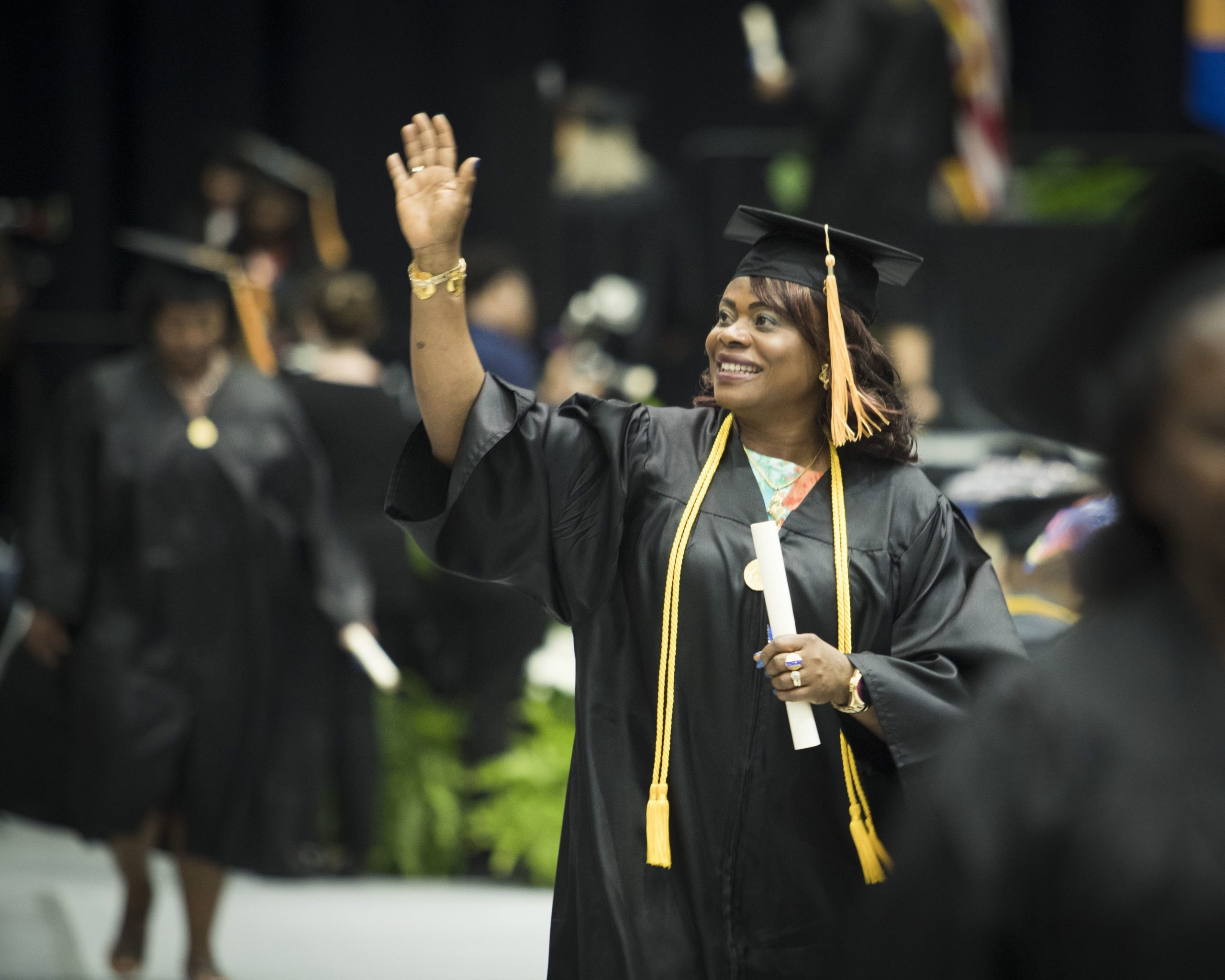 student waving at her family after walking across the stage at UWG's graduation ceremony